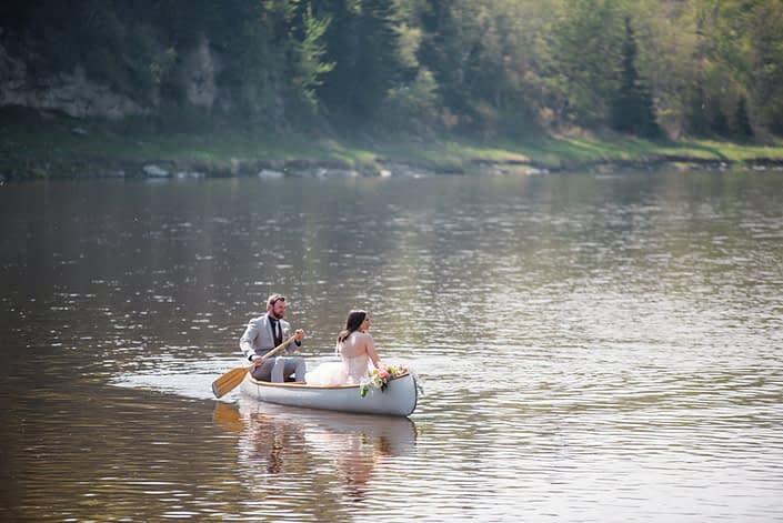 Bride and groom in a canoe on the river. A coral and blush bouquet is laying across the front of the canoe.