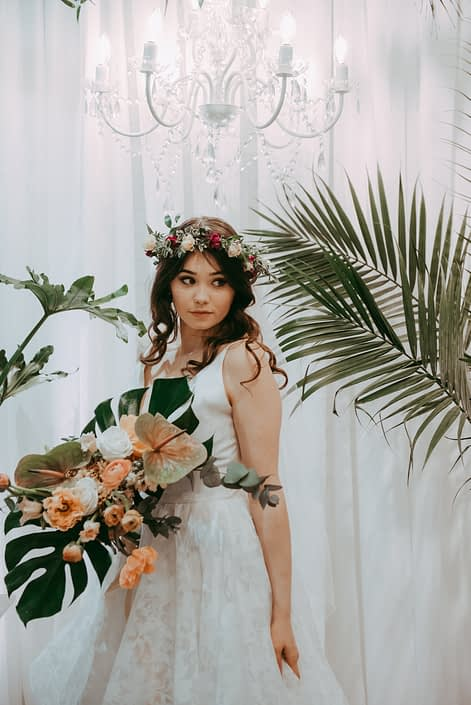 bride with chandelier and white backdrop with tropical plants and bridal bouquet designed with monstera leaves, blush and green anthurium leaves, peach poppies and ranunculus and white roses