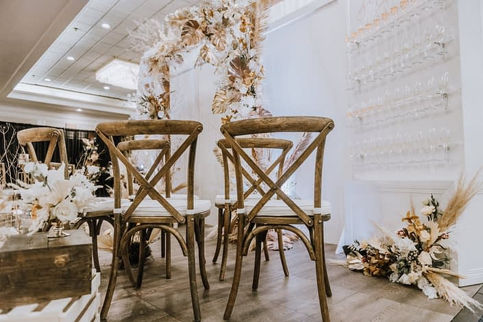 Wooden chairs and wall with champagne glasses and floral arrangement made of pampas grass, white playa blanca roses, orchids, gold painted monstera leaves, and other dried foraged leaves and branches.