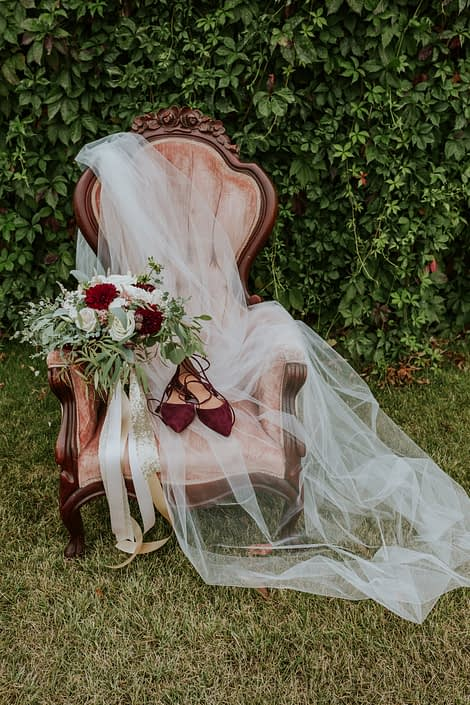 Antique dusty rose armchair with cathedral veil, burgudy heels and burgundy, blush and ivory bouquet with eucalyptus greenery