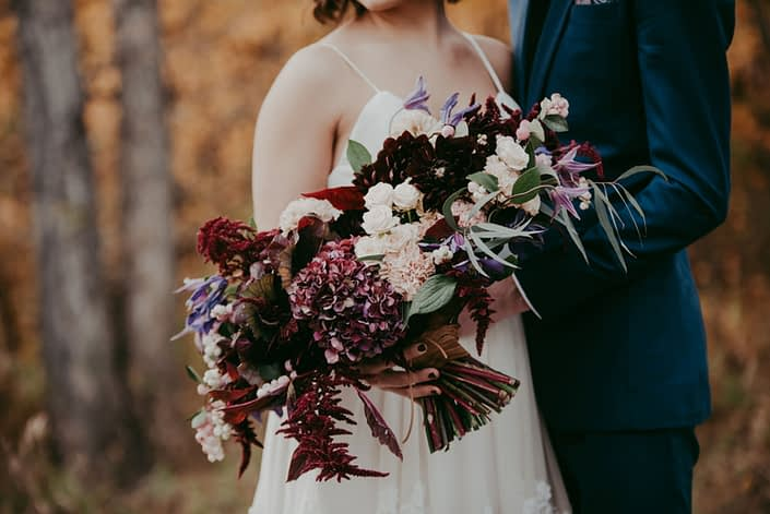 Close up of bridal bouquet designed with burgundy amaranthus and hydrangea blush carnations and spray roses and purple clematis with groom in navy blue suit