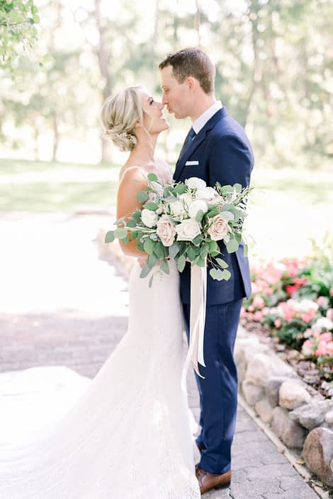 Bride and groom with a timeless white wedding bridal bouquet designed with white o'hara garden roses, quicksand roses, white ranunculus, white astilbe, olive branches and fresh eucalyptus greenery.