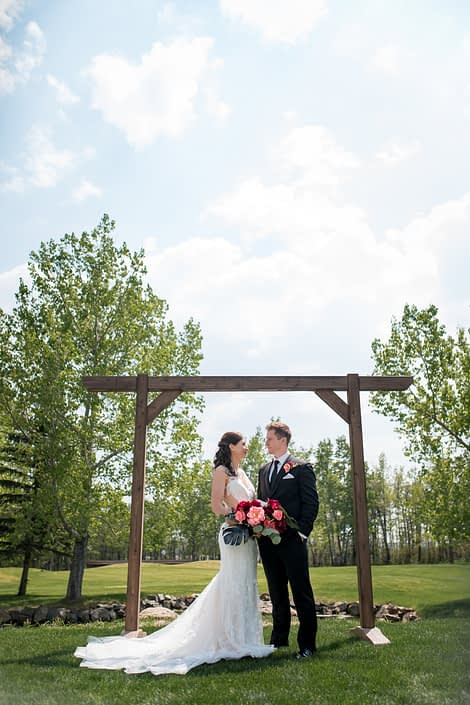 bride and groom under wooden archway holding a bouqute designed with burgundy and coral peony, eucalyptus and black monstera leaves