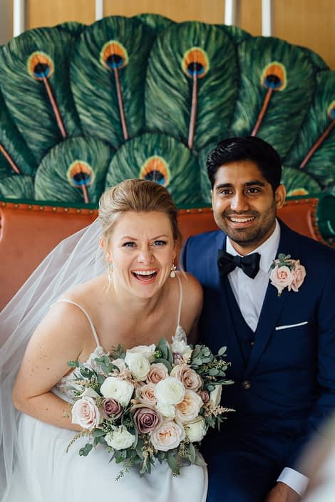 Jill and Jason at the Calgary Zoo; bride holding romantic blush bridal bouquet featuring white o'hara garden roses, quicksand roses, white ranunculus and pale pink astilbe with eucalyptus greenery; groom wearing light pink spray rose boutonniere.