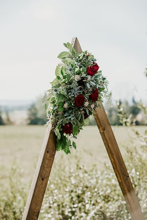 Burgundy and royal blue flower arrangement atop a wooden triangle archway designed with black bacarra roses, ranunculus, eryngium, astrantia, blue viburnum berries and salal and eucalyptus greenery