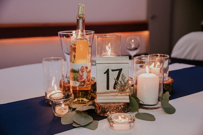 Centrepiece for Brooke and Levi's Rustic Chic Blush Wedding. Created with pillar candles, tree cookies, white painted table numbers, and eucalyptus leaves.