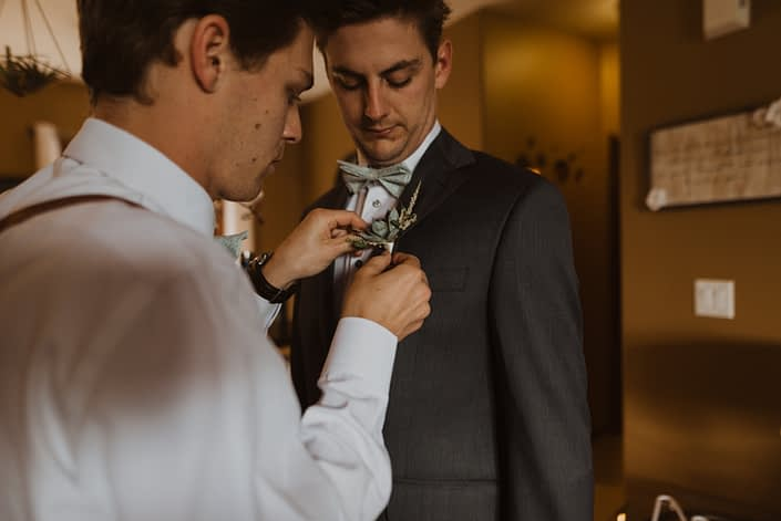 Groom getting his boutonniere pinned on; it was designed with a single small succulent accented by white astilbe and a touch of greenery.