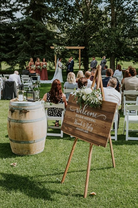 Rusty Rose Wedding at Hilltop Outdoor Ceremony featuring welcome sign with floral piece, lanterns and archway arrangement