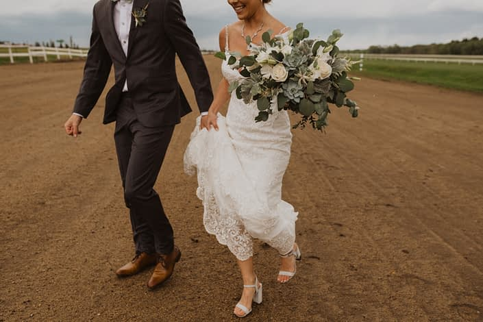 Bride and Groom walking at Track on 2 with a white and grey green bridal bouquet featuring Playa Blanca roses, lisianthus, astilbe, blue star succulents, dusty miller and a mixed variety of eucalyptus.