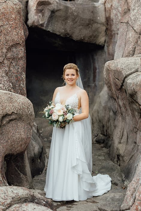 Bride, Jill, at the Calgary Zoo holding romantic blush hand-tied bouquet designed with white o'hara garden roses, quicksand roses, white ranunculus, and light pink astilbe with eucalyptus greenery.