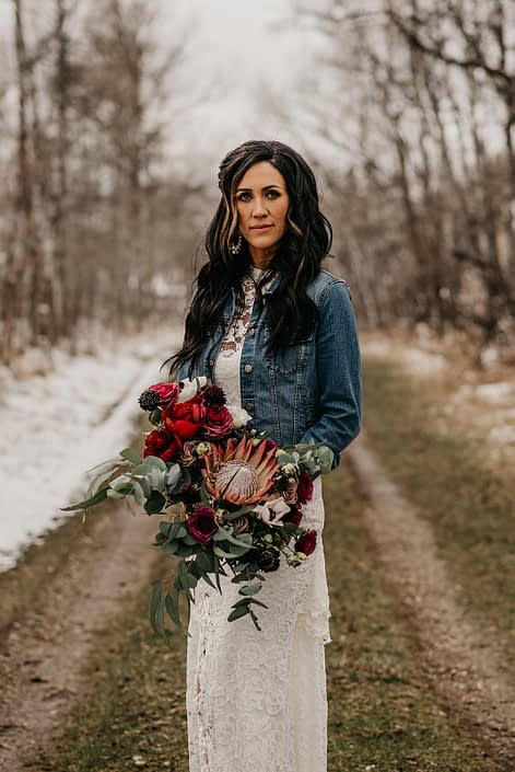Rustic Boho Chic Wedding - Bride wearing ivory lace dress and jean jacket holding bridal bouquet made of king protea, red peonies, pink roses, plum scabiosa, panda anenome, and eucalyptus greenery.