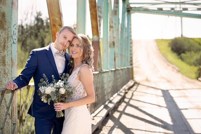 Bride and groom under a blue bridge with a blue and white bridal bouquet featuring panda anemones, ranunculus, roses, eryngium, and delphinium