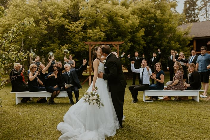 Bride and groom kissing after ceremony at Diamond in the Rough, rural Alberta wedding venue; white bridal bouquet