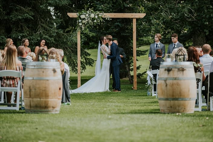 Bride and groom kissing under archway arrangement at Hilltop outdoor ceremony