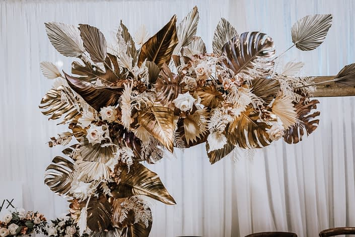 Dramatic archway arrangement at the With This Ring Bridal Gala 2020. It was designed with metallic gold monstera leaves and anahaw palm leaves, blush pink and ivory roses and other cream coloured dried foliage.