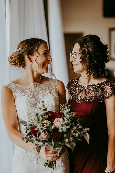 Tanya and Sean's RCMP Wedding - bride and mother with bridal bouquet designed with burgundy dahlias, eryngium, amnesia roses, black baccara roses, rose gold painted succulents and eucalyptus greenery