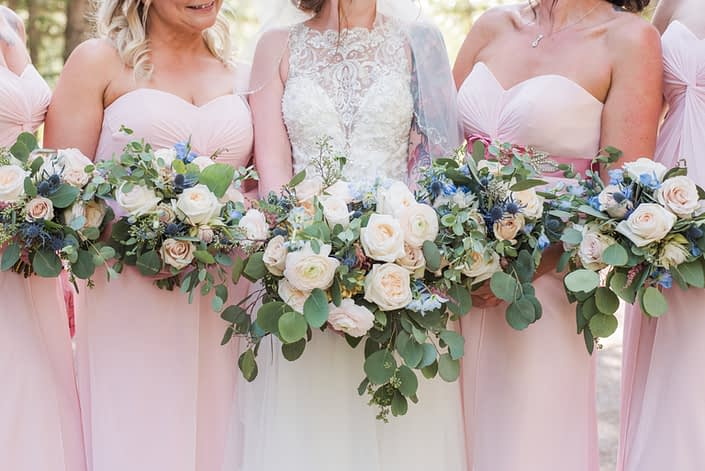 Close up of Amy and her bridesmaids' pink and blue bouquets designed with white o'hara garden roses, quicksand roses, ranunculus, delphinium, astilbe, eryngium and eucalyptus.