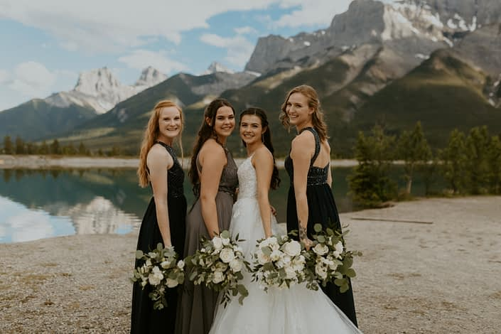Bride and bridesmaids holding white bouquets in the mountains; bouquets included roses, ranunculus, lisianthus