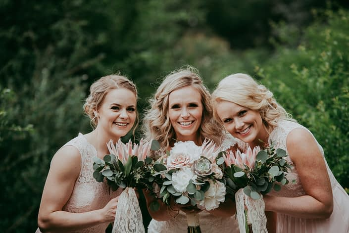 Blond bride and bridesmaids in blush wedding dresses holding bouquets of silver dollar eucalyptus and pale pink king protea with white peony and succulents