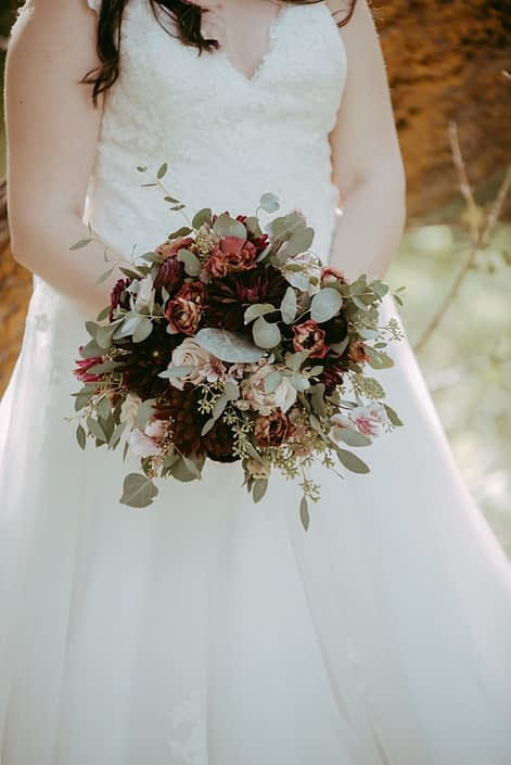 Rustic burgundy and dusty rose bridal bouquet designed with pale pink astilbe, burgundy dahlias, brown lisianthus, burgundy ranunculus, quicksand roses and eucalyptus greenery