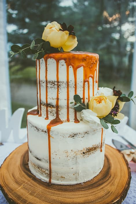 Mustard Yellow wedding cake - naked cake with caramel and cake flowers on a wood cookie.