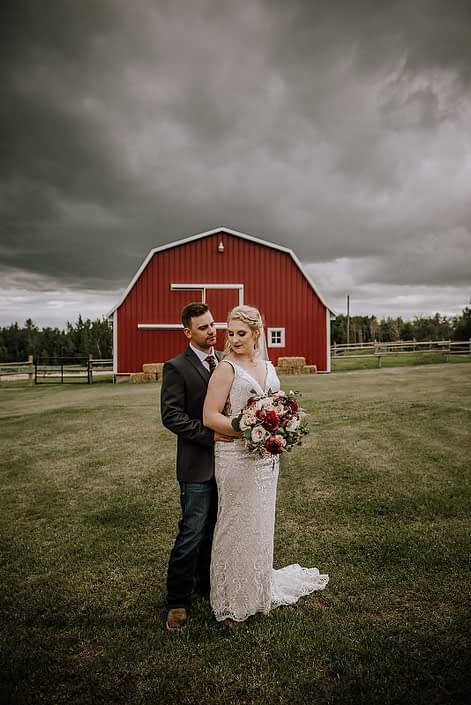 Bride and groom standing in front of a red barn with grey clouds overhead; bride holding a red and blush bridal bouquet featuring red charm peonies, quicksand roses and eucalyptus.