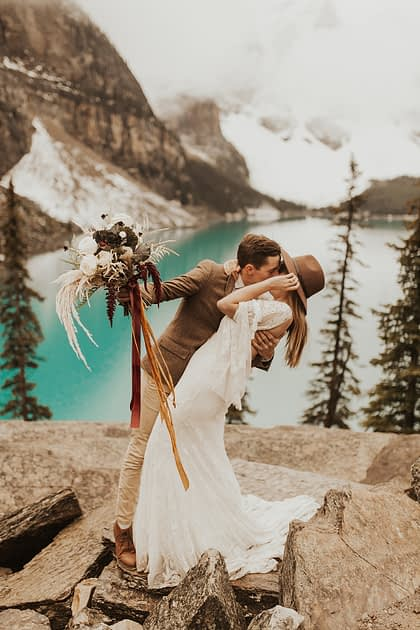 Moraine Lake Elopement Styled Shoot - couple kissing and girl wearing ivory bridal gown and man holding pampas grass bouquet with blush roses and pops of red tied with trailing ribbons.