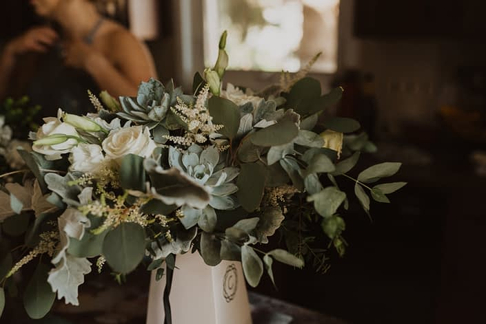 Bridal bouquet featuring white Playa Blanca roses, white lisianthus, white astilbe, blue star succulents, dusty miller and a mixed variety of eucalyptus greenery.