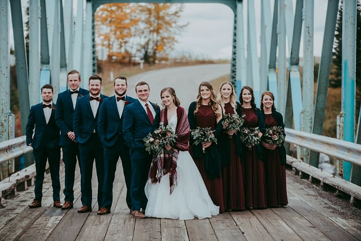bridal party on bridge with blue suits and bowties and burgandy bridesmaid dresses and shawls and bride with plaid shawl and bouquets with mixed eucalyptus and red roses and burgundy dahlias an blue viburnum berries