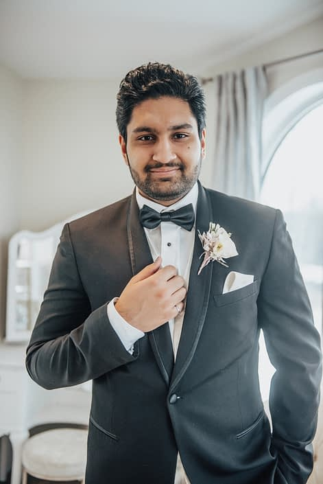Groom in tuxedo with blush boutonniere