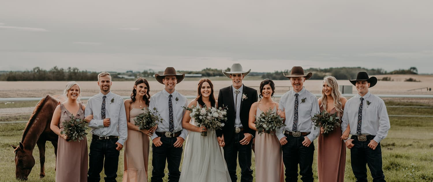 Erika and Colt's blush and mauve country wedding bridal party. The groom and his groomsmen are wearing cowboy hats and boutonnieres, the bridesmaids are wearing mauve dresses and carrying fresh mixed eucalyptus bouquets and the bride is wearing white and holding a blush, ivory and white bridal bouquet featuring roses, ranunculus, anemones and lisianthus.