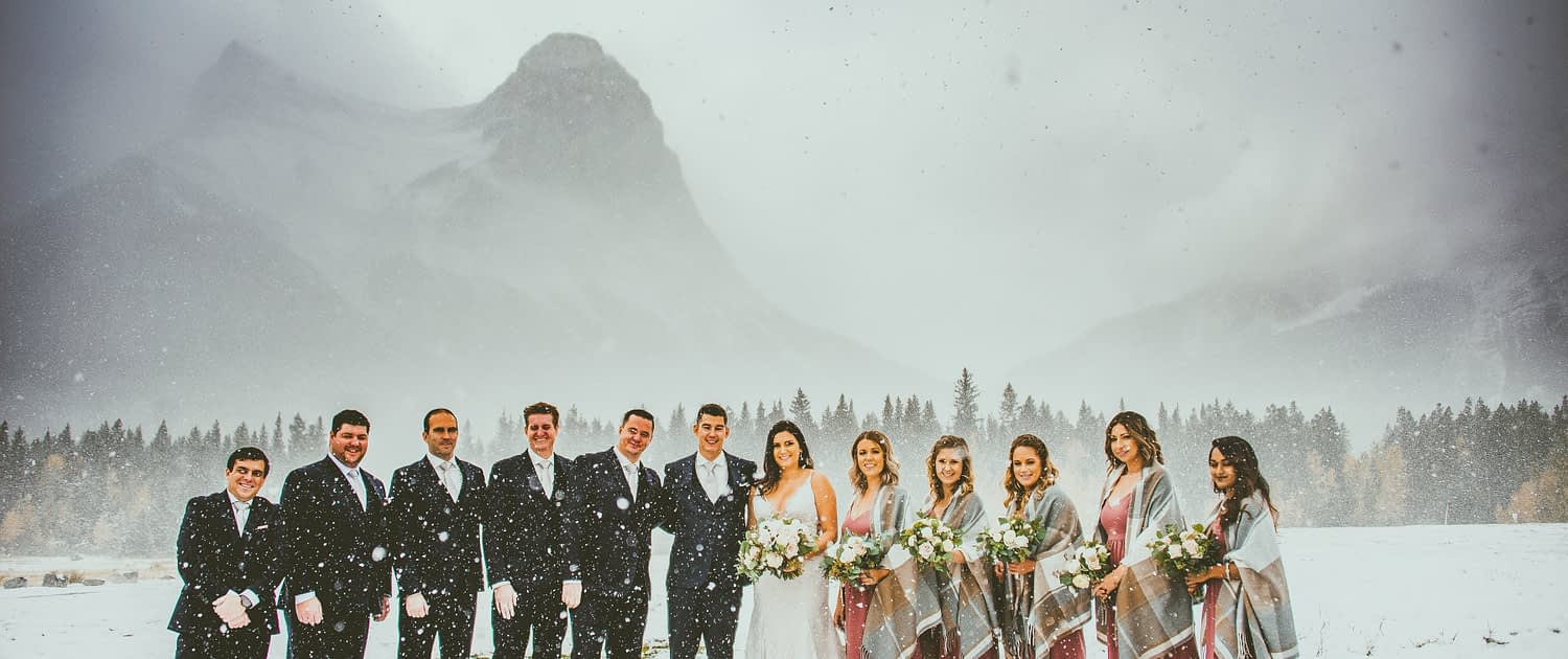Blush and Mauve Canmore Wedding - Meagan and Dwayne's Bridal Party standing in the snowy Rocky Mountains at Canmore. The bridesmaids are wearing mauve dresses and shawls and holding mauve, blush and white bouquets with greenery.