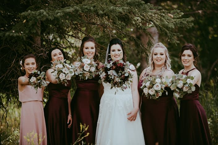 Bride with her bridesmaids and flower girl with burgundy and dusty rose bouquets
