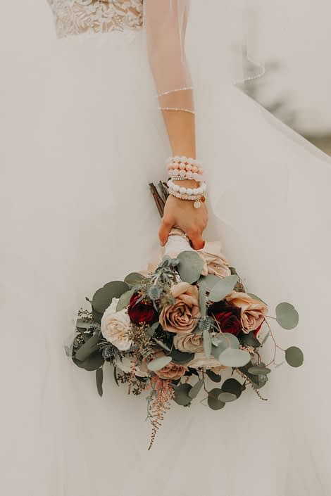 bride with lace dress and stacked bracelets holding a bouquet with quicksand roses and red roses and white o'hara garden roses and pink astilbe and eryngium and seeded eucalyptus and silver dollar eucalyptus