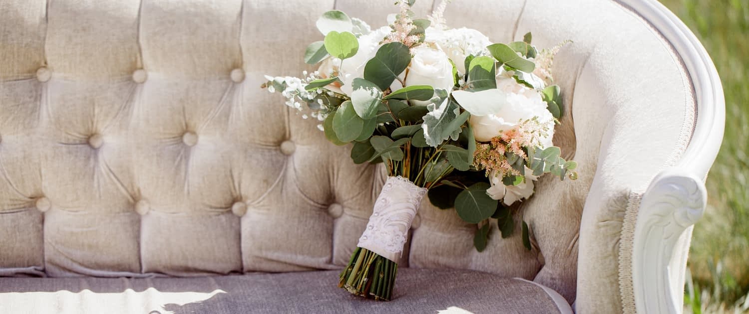 Cream and Blush Bridal bouquet propped on a linen tufted sofa; bouquet features white peonies, white o'hara garden roses, quicksand roses, astilbe, babies breath, dusty miller and eucalyptus with a blush satin and ivory lace overlay wrapped handle.