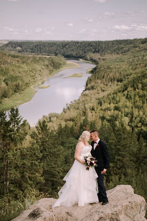 Bride and groom with burgundy and blush bridal bouquet overlooking river valley.