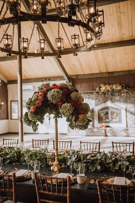 Tall Centerpiece on top of gold candelabra made with green hydrangea and orange dahlias and red blooms accented by a mixed green garland table runner