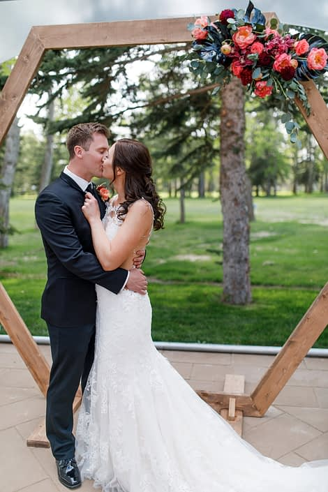 Hexagon archway with bride and groom decroated with a floral piece with black monstera leaves, coral charm peony and burgundy roses
