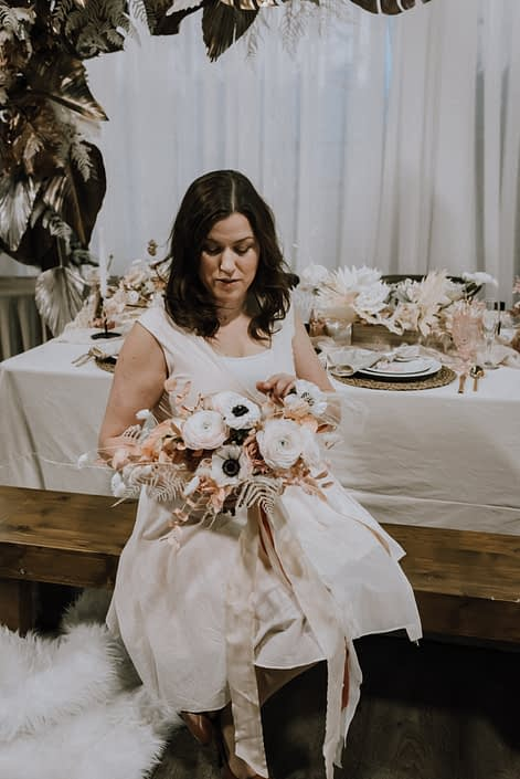 Travis holding a blush pink and white bouquet made of pink dyed eucalyptus, bunny tails, panda anemones, blush pink ranunculus and dried foliage. It was tied with cream coloured trailing ribbons.