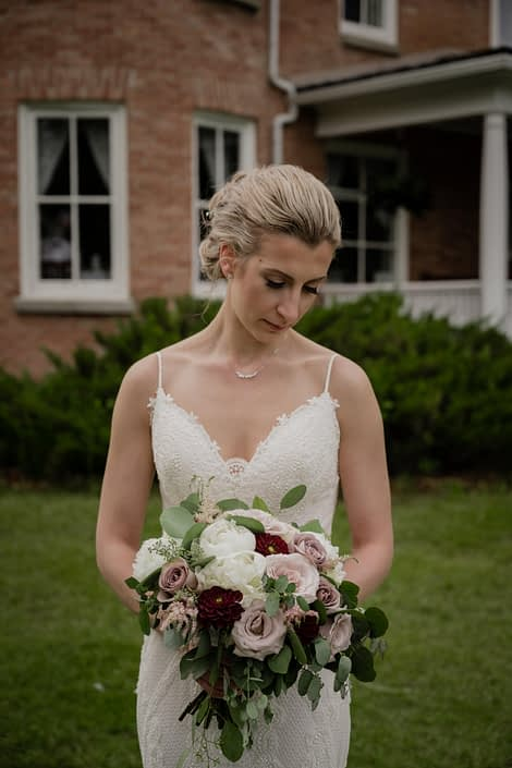 Bride looking at burgundy and mauve bridal bouquet featuring dahlias, peony, ranunculus, amnesia roses and quicksand roses.