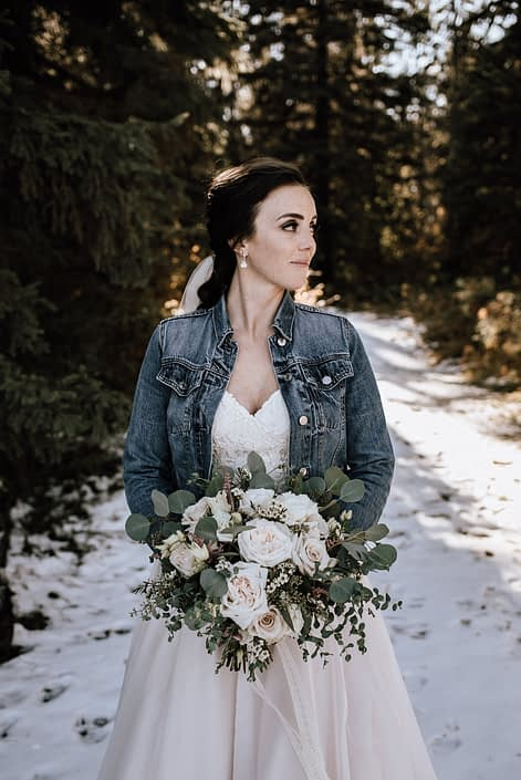 Bride in jean jacket with bouquet of playa blanca white roses and eucalyptus