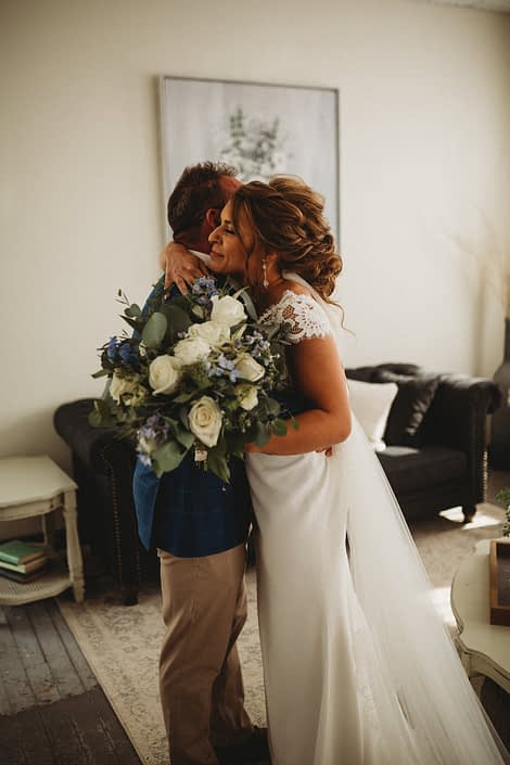 Bride hugging father with blue and white bridal bouquet designed with Tibet roses, ranunculus, astilbe, delphinium, eryngium and eucalyptus.