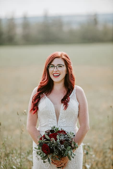 Hailey, holding burgundy bridal bouquet with accents of navy blue