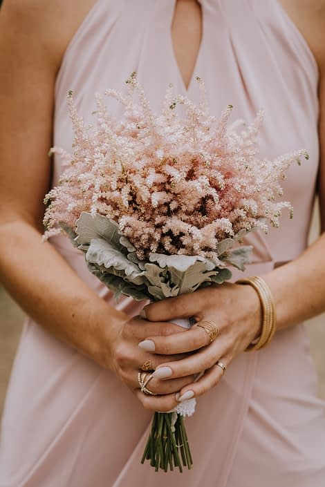 bridesmaid in blush dess holding bouquet of pale pink astilbe with dusty miller collar