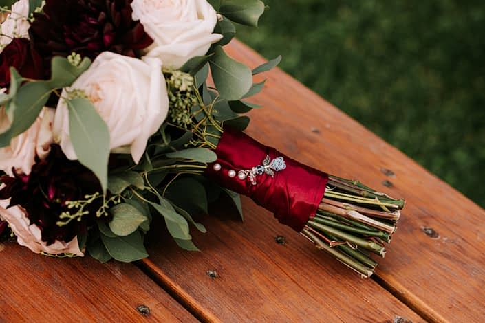 Bridal bouquet wrapped with burgundy satin and finished with bride's charm.