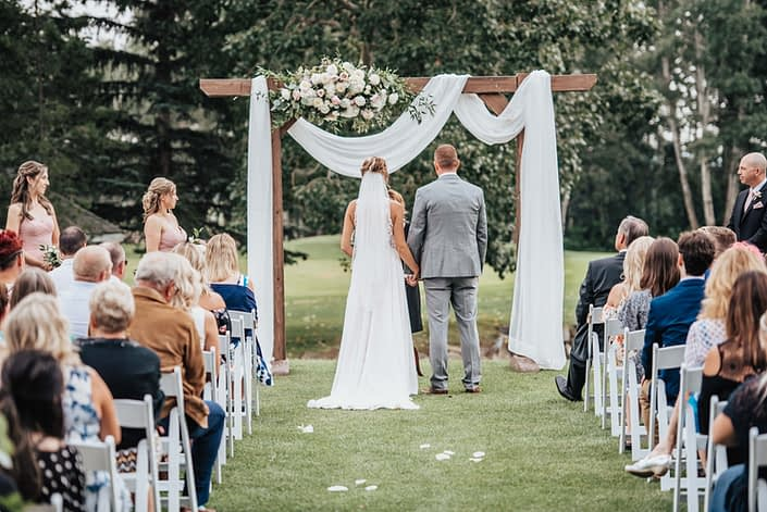 wedding ceremony with floral archway