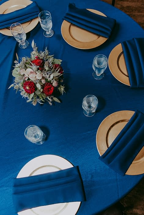 centrepieces for Tanya and Sean's RCMP wedding designed with burgundy dahlias, black baccara roses, navy eryngium and eucalyptus in a compote vase on royal blue linens