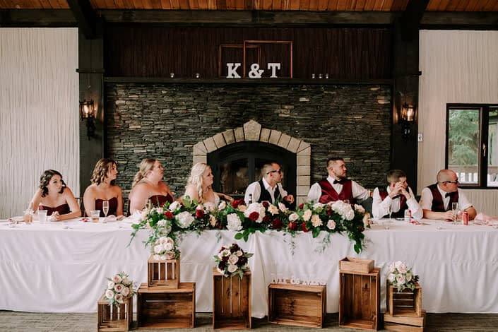 Burgundy and blush head table decorated with flower arrangements in front of a stone fireplace
