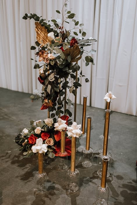 Cambridge Bridal Show 2020 - tall vertical arrangement made of eucalyptus greenery, red and metallic dyed Anahaw palm leaves, and red and blush roses.