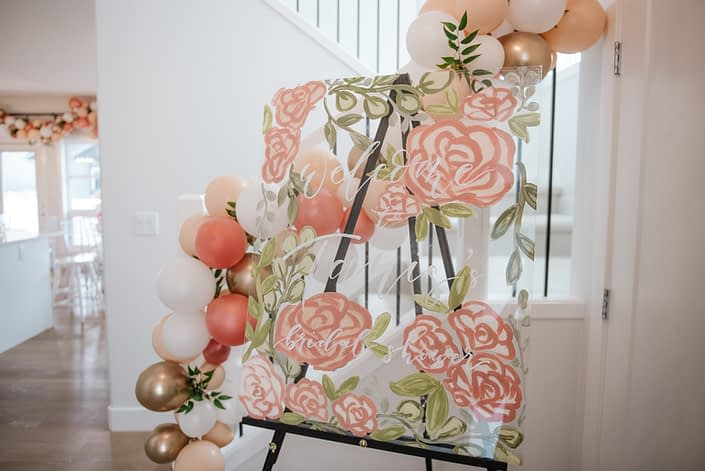Bridal shower welcome sign with balloon garland and accents of italian ruscus in gold, peach and blush